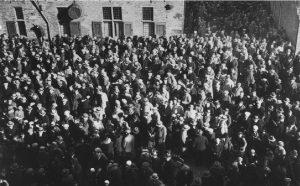 Jaren '30. De Deventer bevolking luistert massaal naar een radio voetbalverslag op de Brink. Op de achtergrond de Waag.
